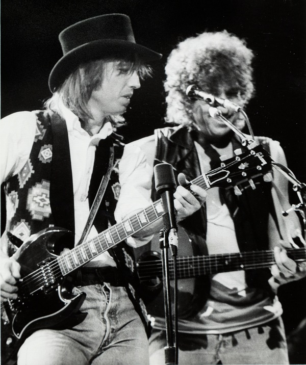 Tom Petty playing the guitar on stage with Bob Dylan in 1987