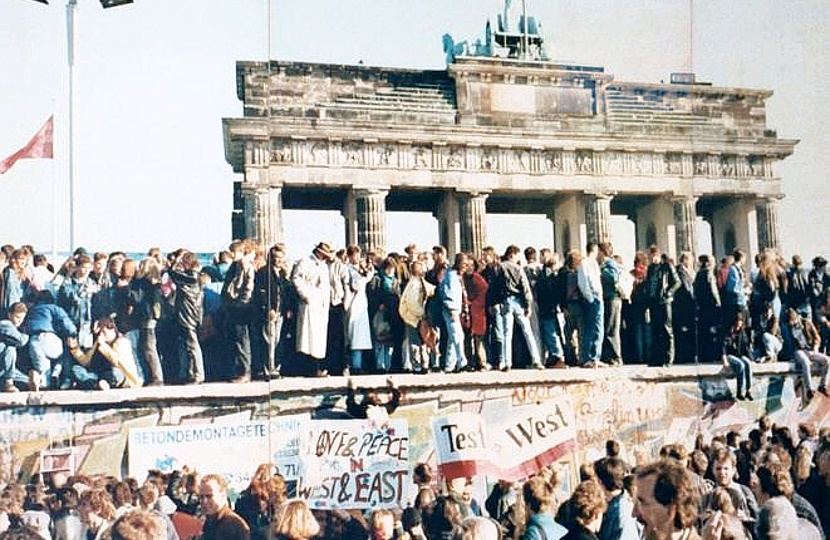 East and West Germans unite on the Berlin Wall at the Brandenburg Gate in 1989
