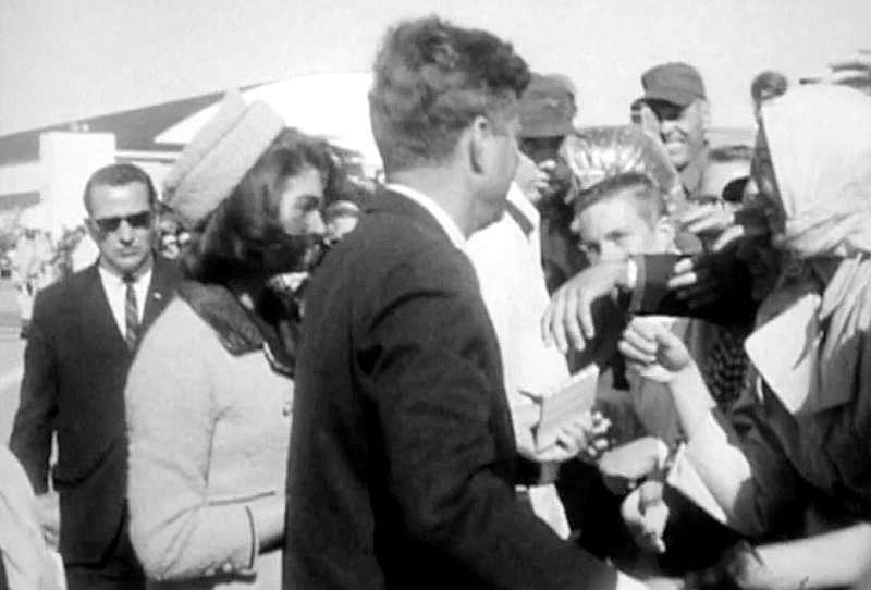 Archive film footage shows Kennedy being handed the notebook to sign by a member of the crowd.