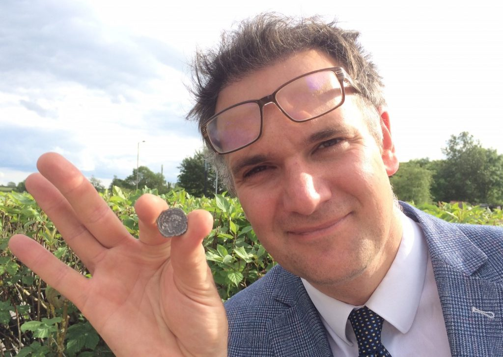 Auctioneer Charles Hanson with the tiny silver Roman coin - the only example of its kind in the world